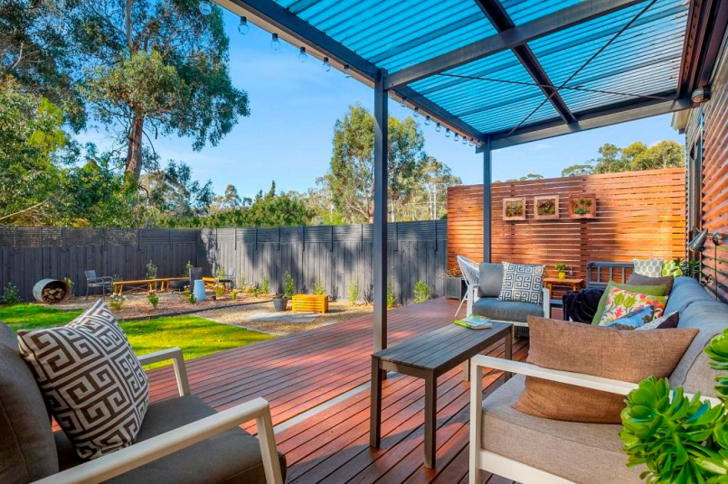Three Beaches Tasmania accommodation rear deck stylishly furnished in dappled sunlight with fountain & firepit area